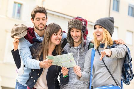 Groep jonge hipster toeristen vrienden juichen met plattegrond van de stad in de oude stad - Reizen lifestyle concept met vrolijke mensen plezier samen - Winter mode kleding draagt met neutrale kleurtinten Stockfoto