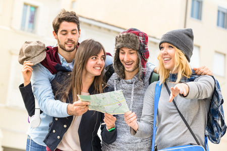 guide: Group of young hipster tourists friends cheering with city map in the old town - Travel lifestyle concept with happy people having fun together - Winter fashion clothing wears with neutral color tones
