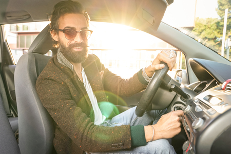 automobile dealership: Young hipster fashion model driving car - Young confident man with beard and alternative mustache smiling looking at camera - Warm filter with soft focus on the face due to natural sun flare halo Stock Photo