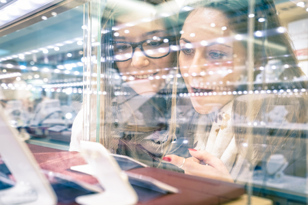 woman window: Young beautiful girlfriends at jewellery store - Best friends sharing free time having fun at shopping mall - People enjoying everyday life moments - Shallow depth of field with focus on woman at left