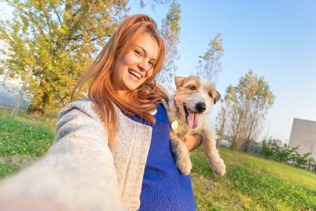 若い赤毛の女性撮影 selfie 屋外でかわいい犬 - 人と動物の愛と友情の概念一緒に - 晴れた冬の午後の暖かい色のトーン - 傾いた地平線組成