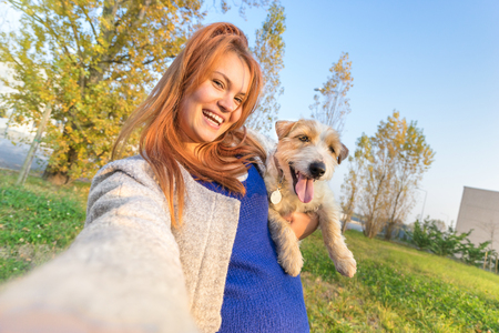 Young redhead woman taking selfie outdoors with cute dog - Concept of friendship and love with people and animals together - Sunny winter afternoon with warm color tones - Tilted horizon composition Archivio Fotografico