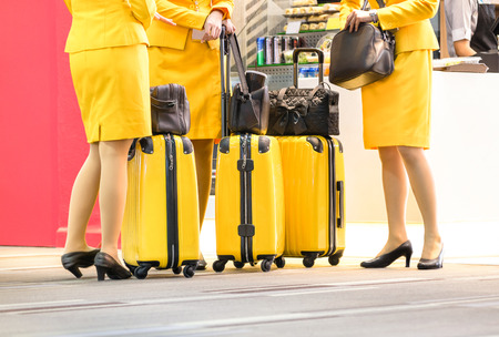 flight crew: Flight attendants at international airport - Working travel concept with women on professional uniform at departure terminal gate ready for boarding - Shallow depth of field with main focus on luggage