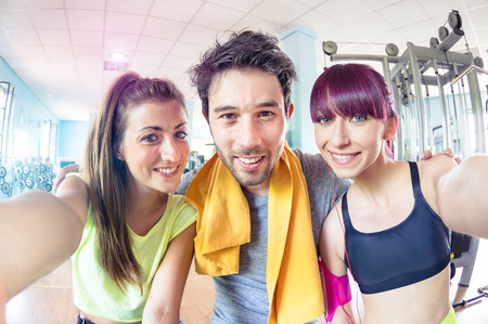 Happy active friends trio taking selfie in gym training studio center - Sporty people ready for fitness time - Healthy lifestyle and sport concept - Soft bright cyan marsala desaturated filtered look