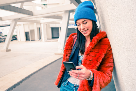 young female: Portrait of happy young woman with smartphone - Fashion hipster girl using mobile smart phone in urban city area - Modern communications lifestyle and new technologies concept - Main focus on the face