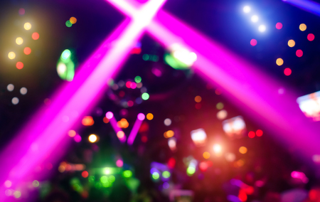 Abstract background with defocused bokeh of laser show in modern disco party night club - Concept of nightlife with music and entertainment - Image with powered colored halos and vivid bright lights Stockfoto