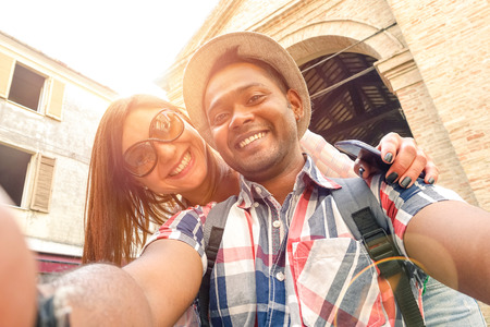Multiracial couple taking selfie at old town trip - Fun concept with alternative fashion travelers - Indian boyfriend with caucasian girlfriend - Warm filter with powered sunlight and lens flare halo