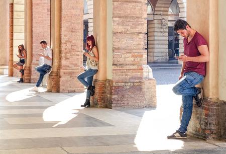 interaccion social: Grupo de amigos jovenes de la manera que usa smartphone en el centro urbano de la ciudad vieja - la adicci�n a la tecnolog�a en el estilo de vida actual con el desinter�s mutuo el uno hacia el otro - las personas adictas a los tel�fonos m�viles modernos