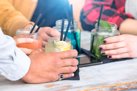 after: Group of friends drinking cocktails at fashion bar restaurants - Side view point of people hands with smartphone - Social gathering concept with addicted men and women - Vivid vintage filter with halo