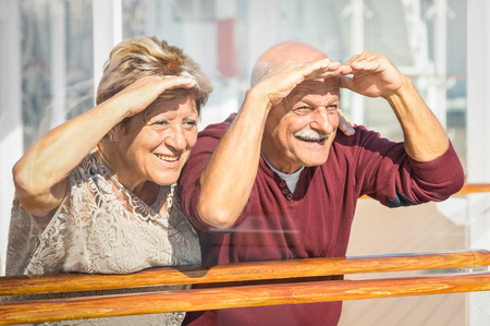 Happy senior couple having fun looking to future - Concept of active playful elderly during retirement - Travel lifestyle with childish funny attitude - Marsala color tone with soft glass reflections