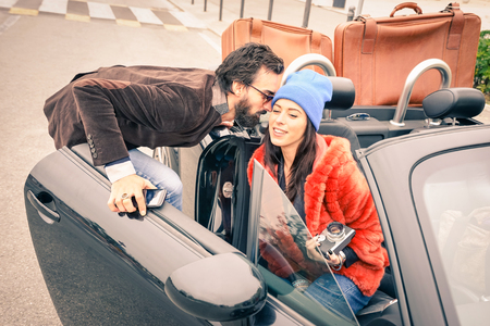 rich life: Confident hipster guy having fun with fashion girlfriend - Happy couple ready to leave for car trip - Modern love relationship concept with people traveling together - Main focus on face of boyfriend