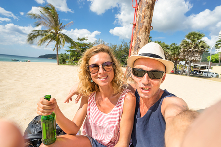 Happy couple taking selfie at beach - Concept of travel lifestyle with young people having fun together - Trip to Thailand in Karon seaside area on Phuket island - Warm color tones and tilted horizon