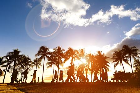 Silhouet van mensen lopen bij zonsondergang op drukke Kalakawa Ave - Front lopen straat promenade van Waikiki Beach in Honolulu Hawaii - Verbeterde zonlicht warme filter met lens flare als onderdeel van de compositie