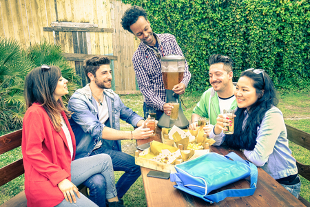 beer garden: Multiracial group of happy friends eating and toasting at garden barbecue party - Concept of happiness with young people outdoors enjoying picnic food together - Vintage filtered look