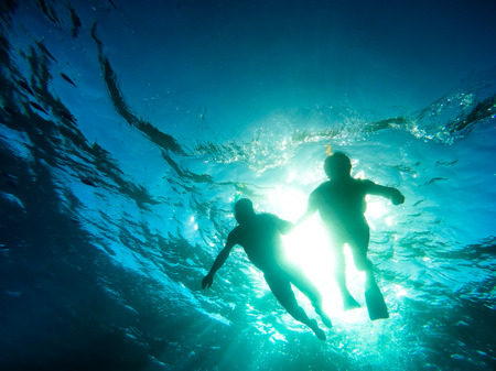 scuba woman: Silhouette of senior couple swimming together in tropical sea - Snorkeling tour in exotic scenarios - Concept of active elderly and fun around the world - Soft focus due to backlight and water density Stock Photo
