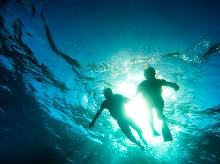 persona de la tercera edad: Silueta de la natación pareja de alto nivel en conjunto en el mar tropical - recorrido bucear en escenarios exóticos - Concepto de ancianos activo y divertido en todo el mundo - El enfoque suave, debido a la densidad del agua y la luz de fondo