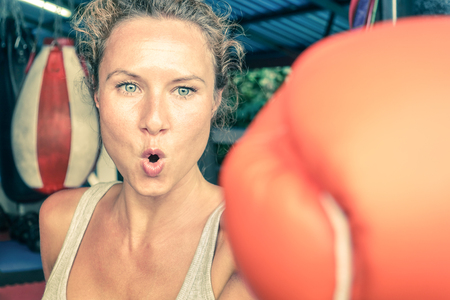 Woman hitting with punch on gritty determination - Fitness boxe and mixed martial arts concept - Fit girl on self defense technique in grungy combat center - Vintage filtered look - Sport gym is setup