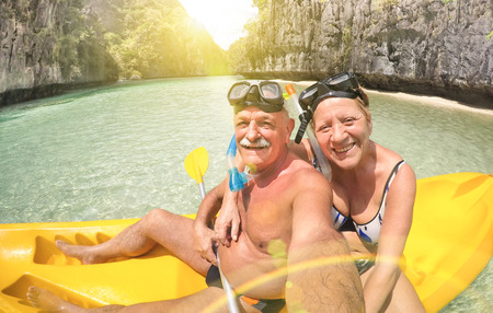 Senior happy couple taking selfie on kayak at Big Lagoon in El Nido Palawan - Travel to Philippines wonders - Active elderly concept around the world - Lens flare and sun halo are part of composition Imagens