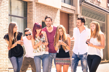Group of young best friends having fun together walking on town street - Moment of technology interaction in everyday lifestyle - Internet connection spots outdoors - Soft desaturated filtered look