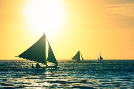 voilier ancien: Silhouette des bateaux typiques de la voile au coucher du soleil dans l'île de Boracay - destination Voyage exclusif aux Philippines - millésime chaud regard filtré