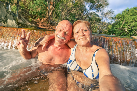 Senior happy couple taking selfie at Maquinit Hot Spring in Coron - Relax concept to Philippines wonders and active elderly traveling around the world - Warm afternoon color tones with tilted horizon Stock Photo