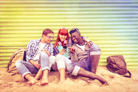 community people: Group of happy multiracial friends having fun together using mobile smart phone - Young hipster people addicted by smartphone on social network community - Multicolored halos on vintage filtered look