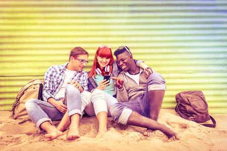 Groupe d'amis multiraciales heureux d'avoir du plaisir ensemble utilisant un téléphone mobile intelligent - Les jeunes hipster accros par smartphone sur la communauté de réseau social - halos multicolores sur cru filtré regard