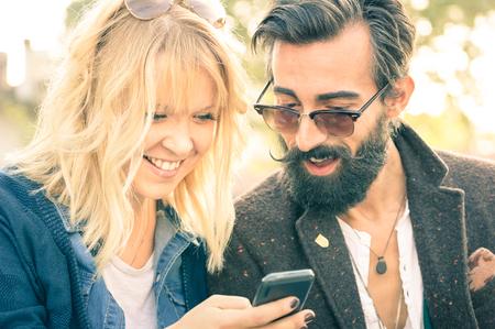 Feliz pareja joven con ropa de época que se divierten con el teléfono inteligente - A partir de la historia de amor con los mejores amigos del inconformista en el teléfono móvil - concepto de adicción con la nueva tecnología - poca profundidad de campo Foto de archivo