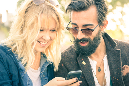 Happy young couple with vintage clothes having fun with smartphone - Beginning of love story with hipster best friends on mobile phone - Addiction concept with new technology - Shallow depth of field