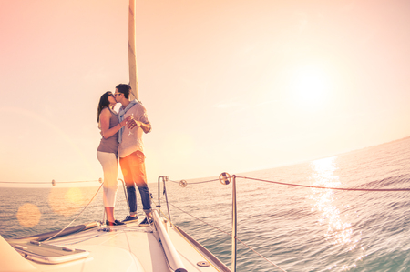 wanderlust: Rich young couple in love on sailboat cheering at sunset - Happy wander lifestyle concept sailing around world - Soft focus on rose quartz filter - Lens flare and tilted horizon as part of composition