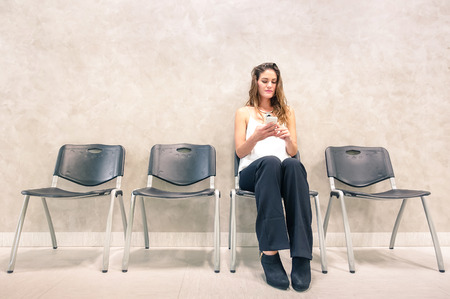 Pensive young woman with mobile smart phone sitting in waiting room - Anxious female person using smartphone in hospital anteroom looking forward for exam test result - Neutral desaturated color tones Stockfoto