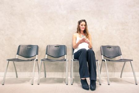 Pensativa mujer joven con el teléfono móvil inteligente sentado en la sala de espera - persona de sexo femenino ansioso con smartphone en la antesala de hospital mirando hacia adelante para el resultado de la prueba del examen - Neutral tonos de color desaturados