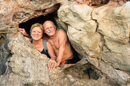 Senior happy couple having fun at the entrance of Kayangan Cave in Coron - Adventure travel in Philippines and asian destinations - Concept of active elderly around the world with no age limitation