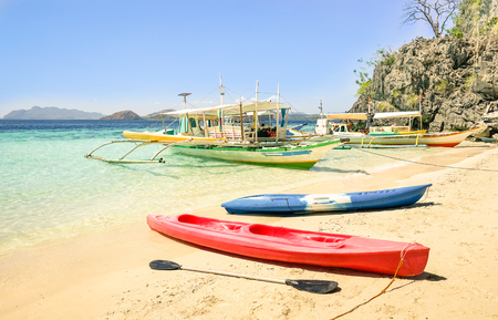 coron: White sand beach with longtail boats and kayaks in Coron Palawan - Beautiful tropical destination in Philippines - Travel concept to nature wonders around the world - Warm sunny afternoon color tones