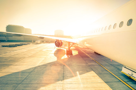 enhanced: Generic airplane on terminal gate ready for takeoff - Modern international airport at sunset - Concept of emotional travel around the world - Wide angle distortion with enhanced sunshine lens flare