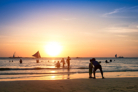 enhanced: Silhouette of unrecognizable tourists and local people with father and son taking selfie at Boracay beach during sunset - Exclusive travel fun destination in Philippines - Warm enhanced filtered look Stock Photo