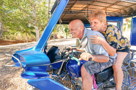retirement: Happy senior couple having fun with tricycle in Philippines travel - Concept of active playful elderly during retirement - Everyday joy lifestyle without age limitation - Warm afternoon color tones