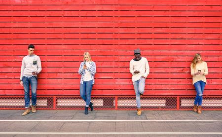 lifestyle: Grupa wielorasowe znajomych mody z wykorzystaniem smartphone z czerwonym tle drewna - uzależnienie technologicznej w miejskim stylu życia z obojętnością wobec siebie nawzajem - osób uzależnionych do nowoczesnych telefonów komórkowych