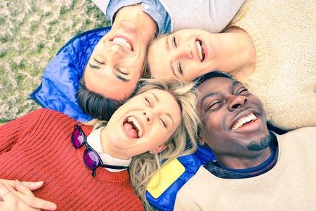 Gemischtrassige beste Freunde, die Spaß haben und zusammen im Freien am Frühjahr lachen - glückliches Freundschaftskonzept mit jungen Leuten auf Modekleidung - umgedrehter Gesichtspunkt - gefilterter Blick der weichen Weinlese Standard-Bild