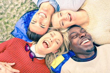 friendships: Multiracial best friends having fun and laughing together outdoor at springtime - Happy friendship concept with young people on fashion clothes - Upside down point of view - Soft vintage filtered look