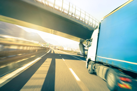 semitruck: Generic semi truck speeding on highway under overpass - Transport industry logistic concept with semitruck container driving fast on speedway - Soft vintage filter with sunshine halo and blurred edges Stock Photo