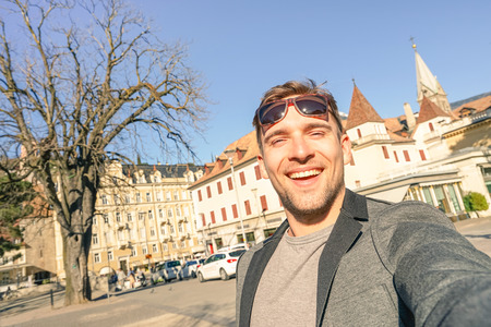 tilted: Young handsome man taking selfie at Meran old town in South Tyrol in Italy - Adventure and travel lifestyle around european destination - Composition with tilted horizon and warm afternoon color tones