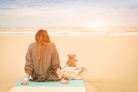ragazza innamorata: Giovane donna seduta singolo in spiaggia con orsacchiotto guardando il mare - concetto di solitudine e la solitudine con l'amicizia immaginario e sentimenti malinconici - Filtro annata calda con una maggiore sole