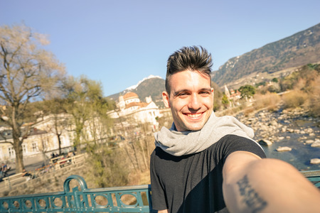 meran: Young handsome man taking selfie by Passer river at Meran old town in South Tyrol in Italy - Adventure and travel lifestyle concept - Composition with tilted horizon and warm afternoon color tones
