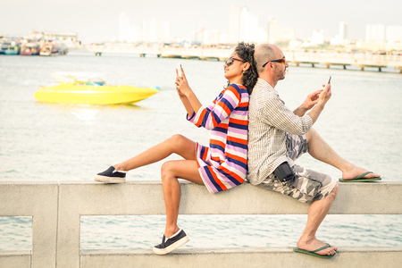 disinterest: Travelers couple in disinterest moment with mobile phones at Pattaya beach Stock Photo