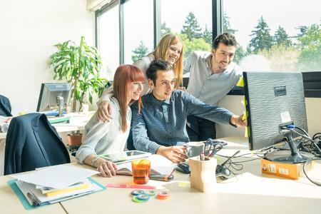 empresas: Grupo de trabajadores jóvenes empleados con el ordenador en el estudio urbano alternativo