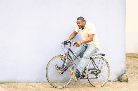 migrant: African american guy having fun with vintage bicycle