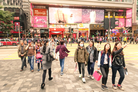 china people: HONG KONG - 22 FEBRUARY 2015: crowd of multiracial people crossing the road on Nathan Street near Tsim Sha Tsui in city heart of Hong Kong; special administrative region of Peoples Republic of China Editorial