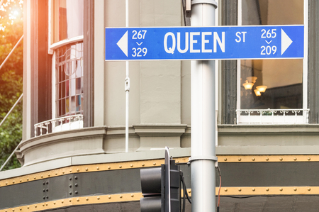 new direction: Street sign of Queen Street in Auckland - Urban concept and road direction in the biggest city of New Zealand - Australasian world famous destination with warm filter and enhanced sunshine halo Stock Photo