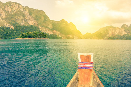 ang: Point of view of Cheow Lan lake from long tail boat - Khao Sok National Park in Thailand - Adventure travel concept with wanderlust feelings - Enhanced sunflare halo with vivid vintage filter